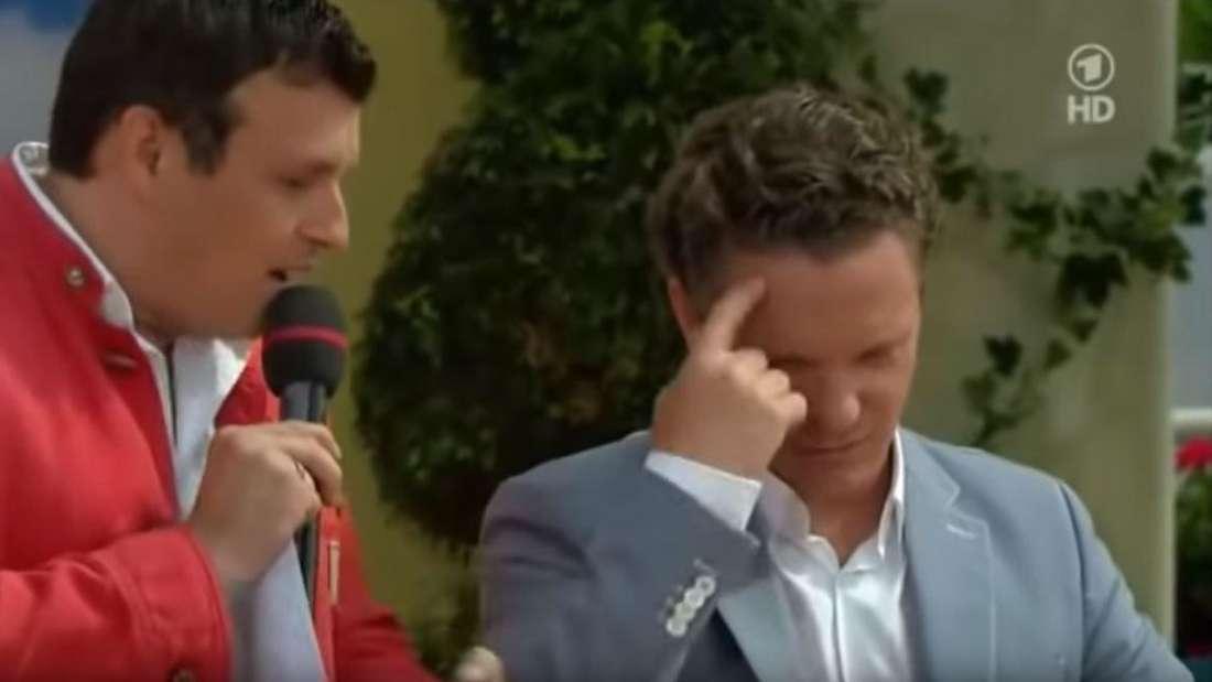 """Trompeter Stefan Mross überlegt bei """"Immer wieder sonntags"""" in der ARD, ob er eine sehr scharfe Currywurst essen soll."""