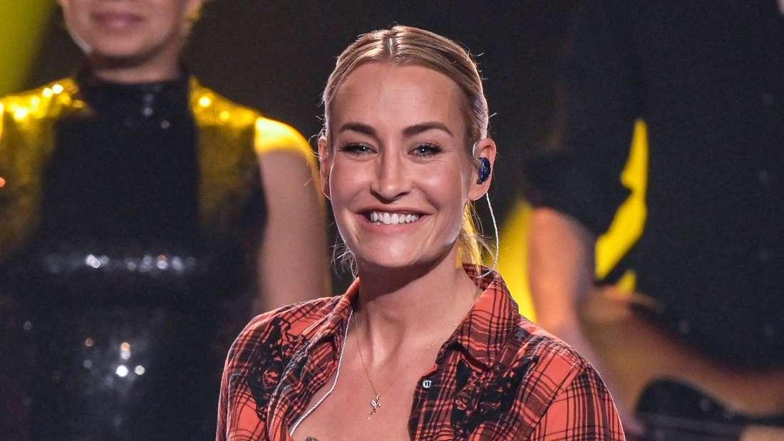 Sarah Conner ist Sängerin. Sie lacht und trägt ein rotes Hemd auf einem Konzert