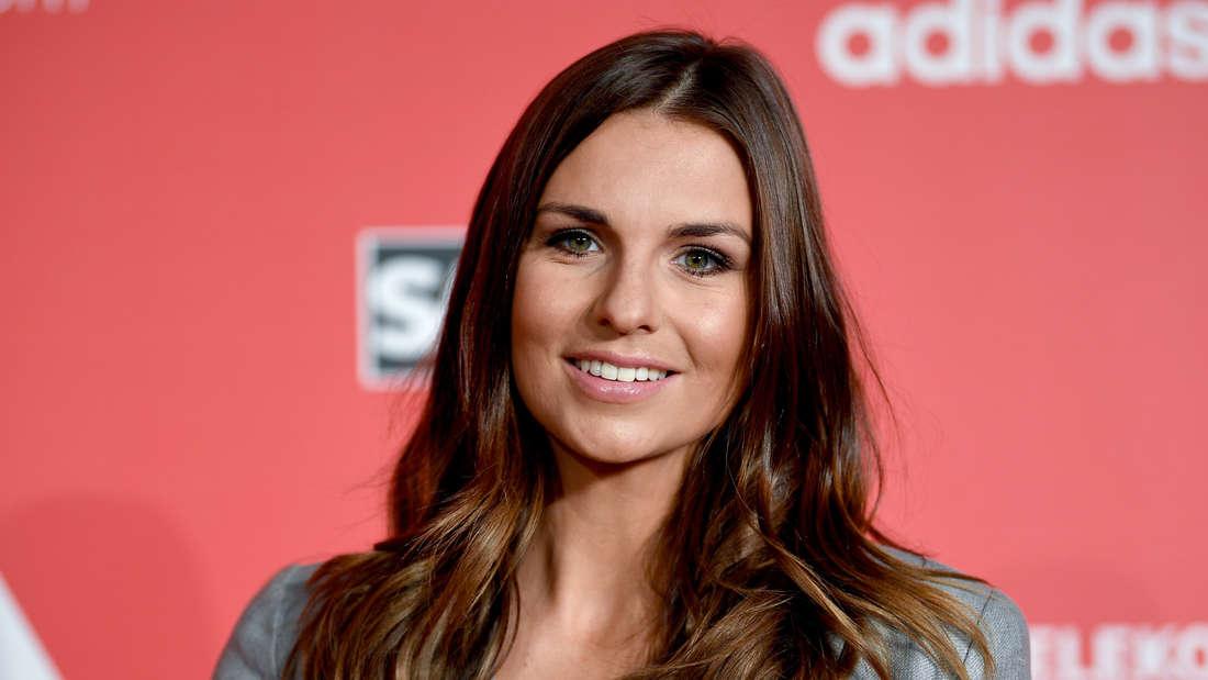 Laura Wontorra steht vor einer Adidas Wand.