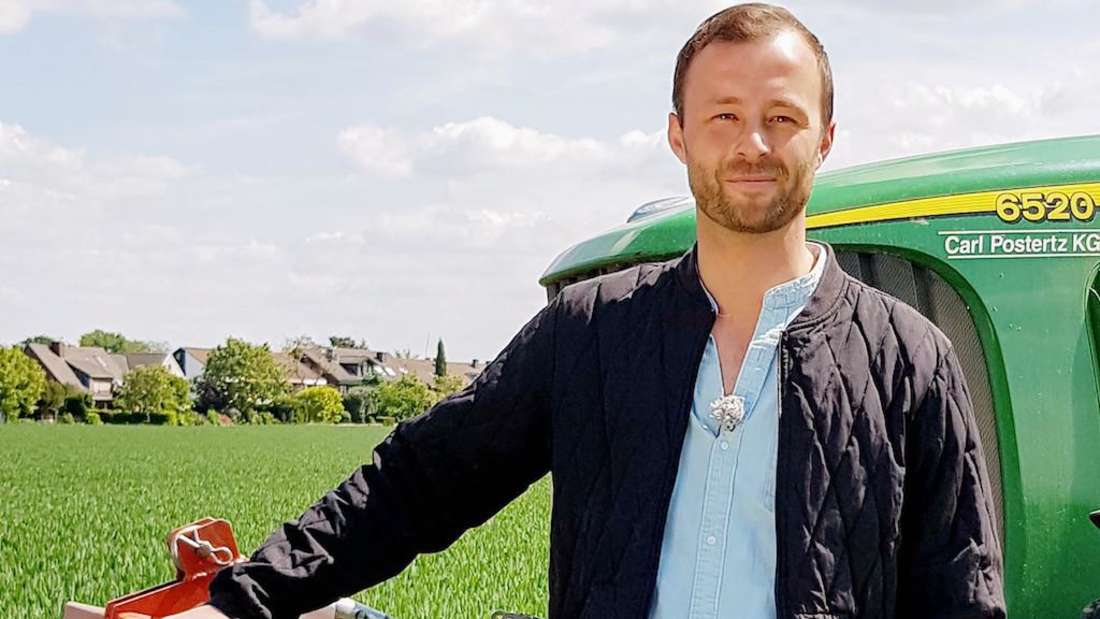 """""""Bauer sucht Frau""""-Kandidat Peter lehnt an einem Traktor und blickt in die Kamera"""