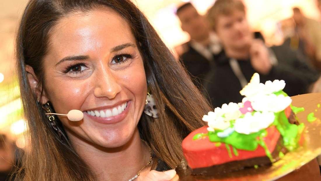 Sarah Lombardi hält einen Kuchen in der Hand und lächelt in die Kamera