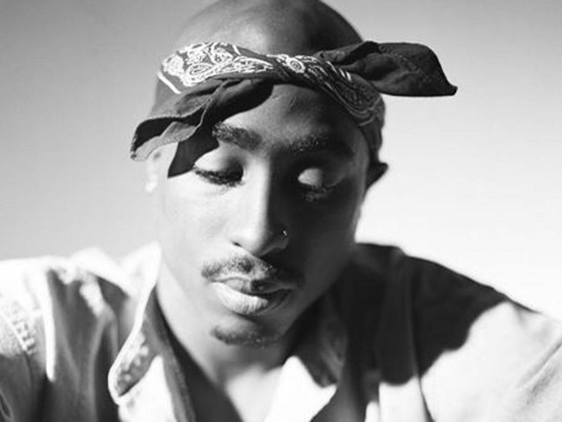 Rapper Tupac ist auf dem s/w Foto zu sehen. Er trägt sein typisches Kopftuch und schaut verträumt nach unten