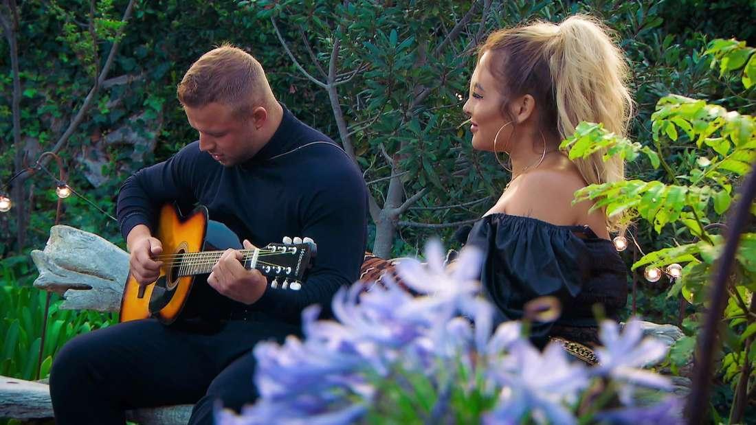Juliano spielt Laura etwas auf der Gitarre vor