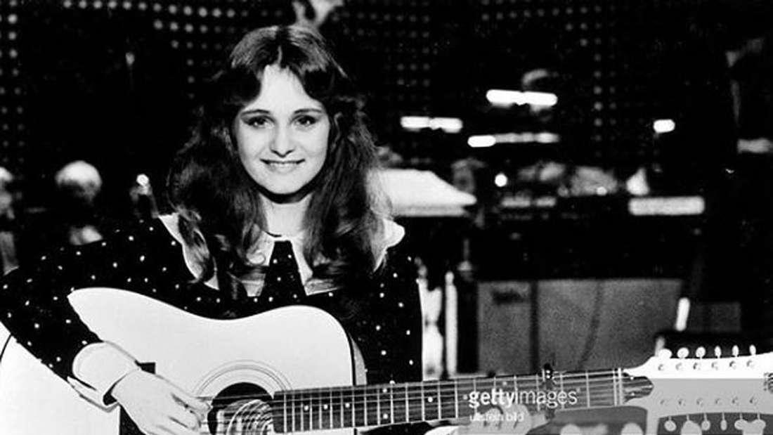 s/w Bild von 1982. Nicole lächelt in die Kamera und hält ihre Gitarre in den Händen. Im Hintergrund die Eurovision Song Contest Bühne