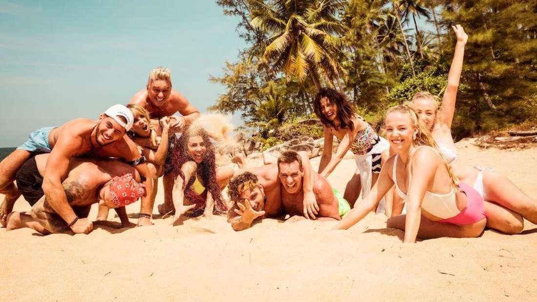 """Ein paar der Kandidaten von """"Kampf der Realitystars - Schiffbruch am Traumstrand"""" lächelnd am Strand"""