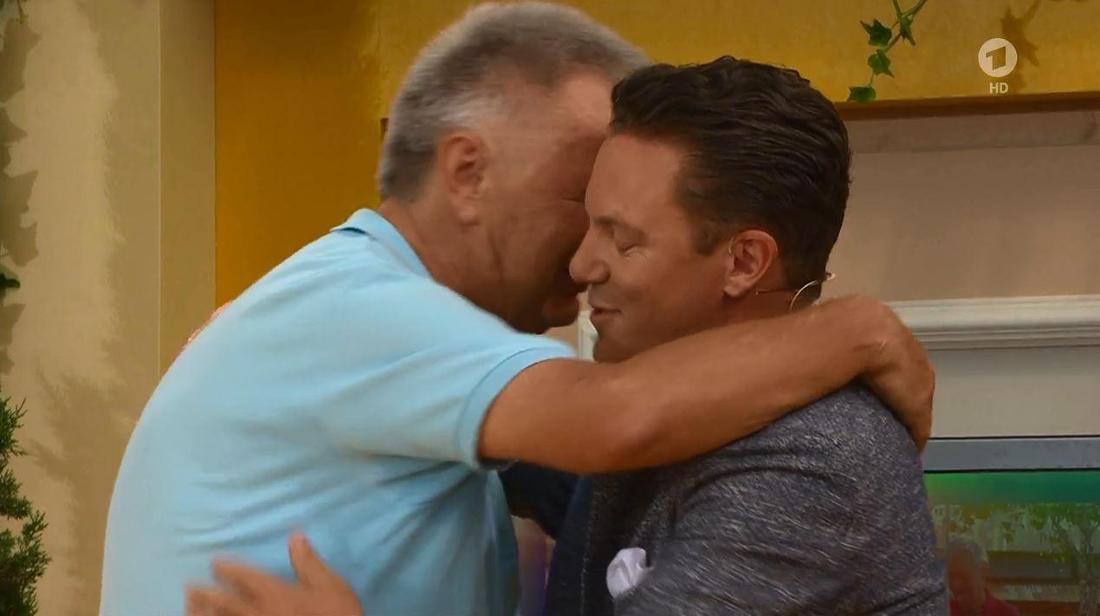 """Stefan Mross und Überraschungsgast Rainer Meutsch umarmen sich in der Schlagershow """"Immer wieder Sonntags"""" (Screenshot)"""
