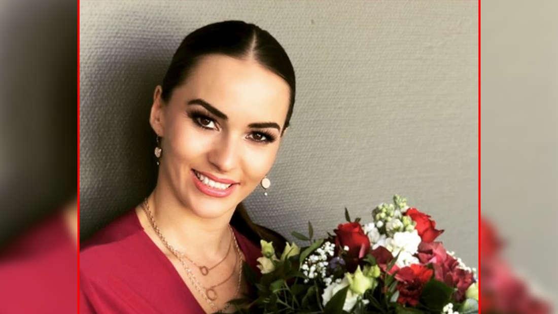 Renata Lusin hält einen Blumenstrauß in der Hand. (Screenshot)