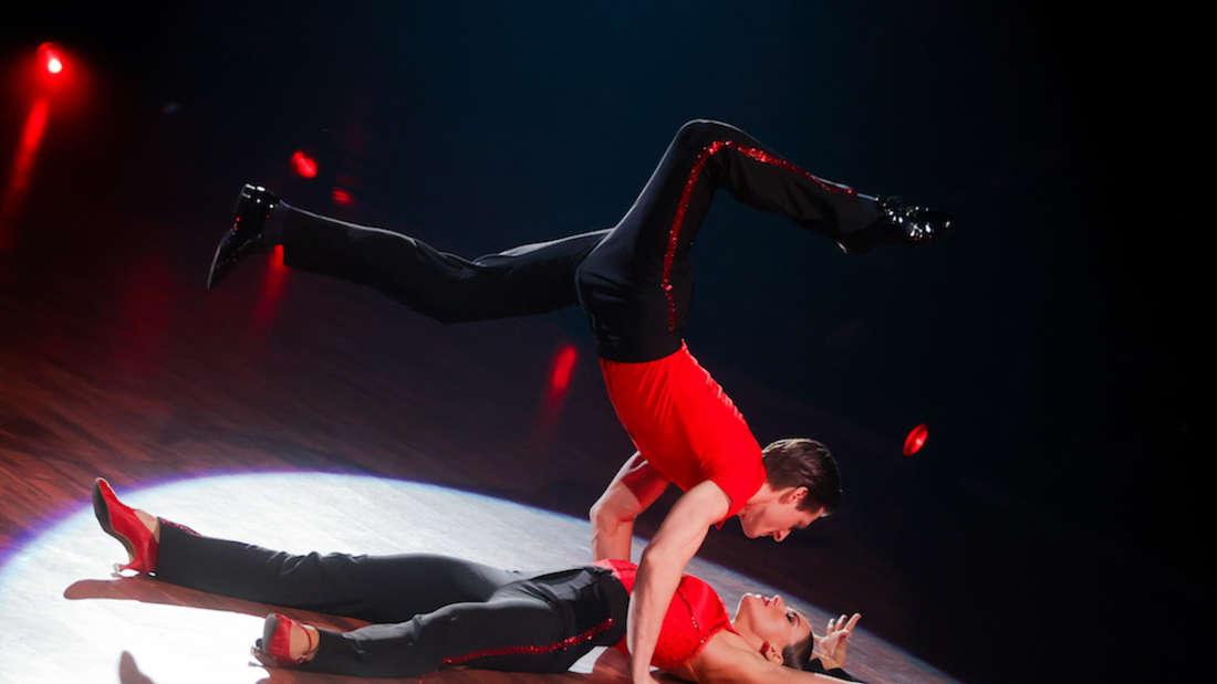 Renata Lusin liegt auf dem Tanzparkett, Moritz Hans beugt sich über sie