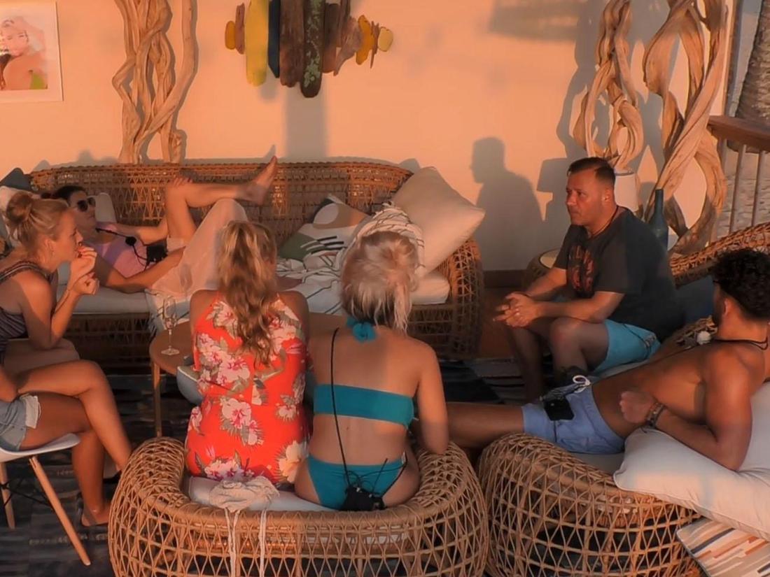 """Die """"Kampf der Realitystars""""-Teilnehmer sitzen um einen Tisch und hören der Geschichte von Willi Herren zu"""