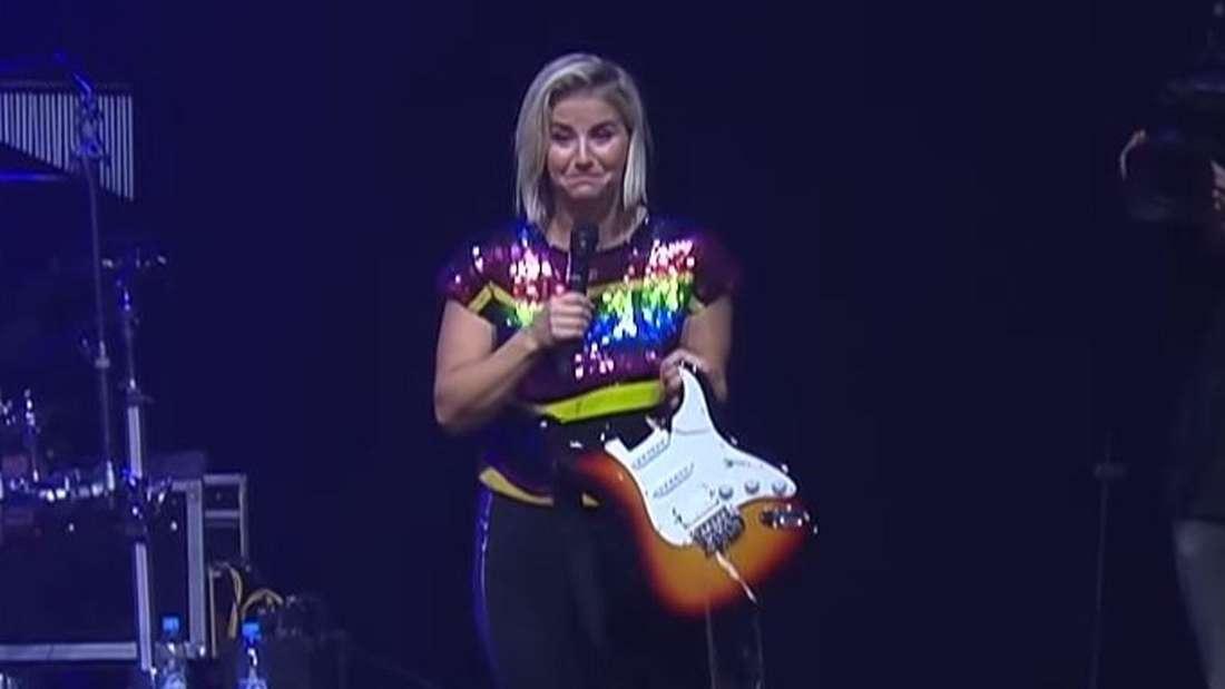 Beatrice Egli steht auf der Bühne und hält eine kaputte Gitarre in der Hand