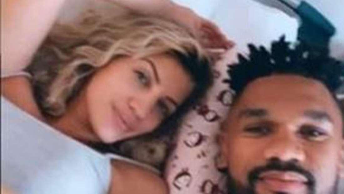 Sarah und Dominic Harrison liegen in einem Krankenhausbett und schauen hoch zur Kamera