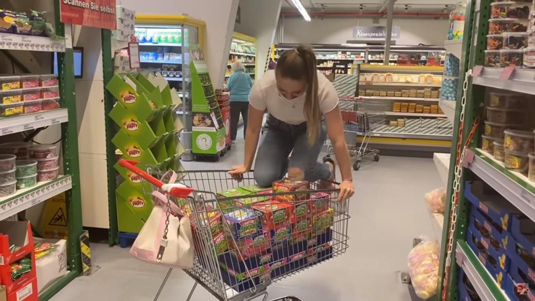 Bibi klettert auf den Einkaufswagen, der voll mit Kaugummi-Packungen ist