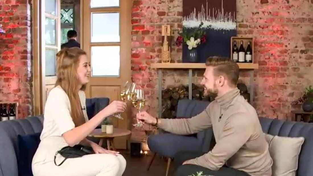 Zwei Singles sitzen in einem Cafe und prosten sich mit einem Sektglas zu