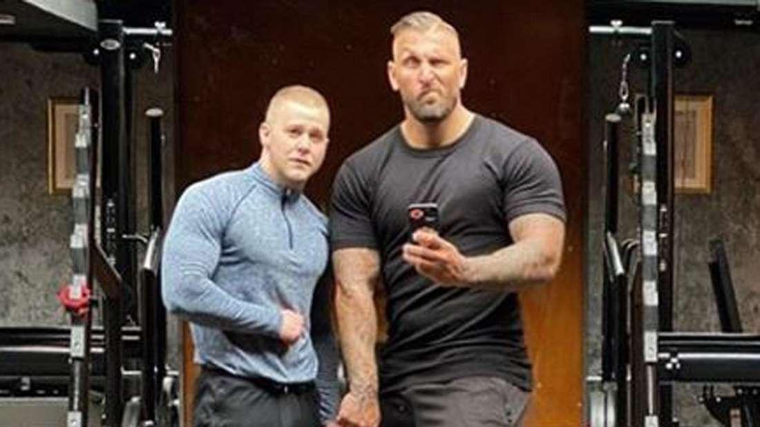 Felix van Deventer steht neben einem Kollegen in einem Fitness-Club und hat muskulöse Oberarme