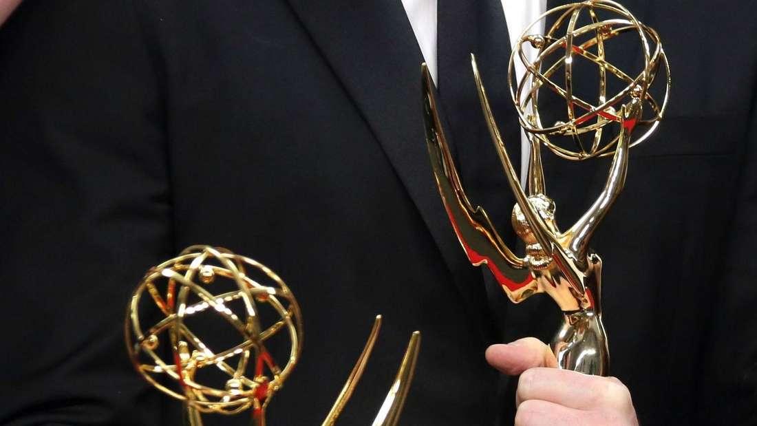 Es sind Hände zu sehen, die zwei Emmys in den Händen halten