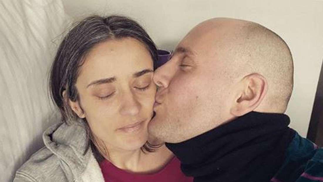 Oli P. gibt Pauline einen Kuss, die in einem Bett liegt