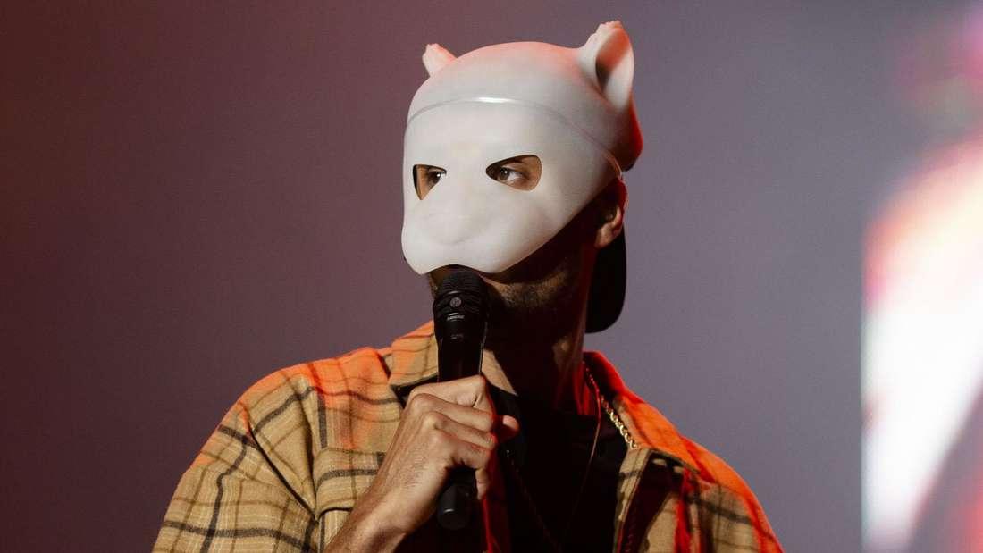Cro steht auf der Bühne mit der Panda-Maske