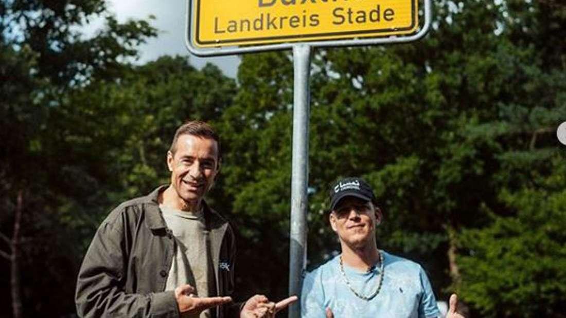 Montanablack und Kai Pflaume stehen vor dem Ortseingangsschild von Buxtehude