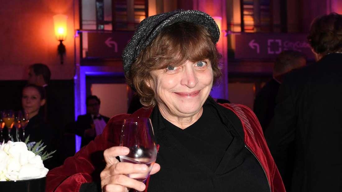 Katharina Thalbach prostet mit einem Glas Sekt in die Kamera