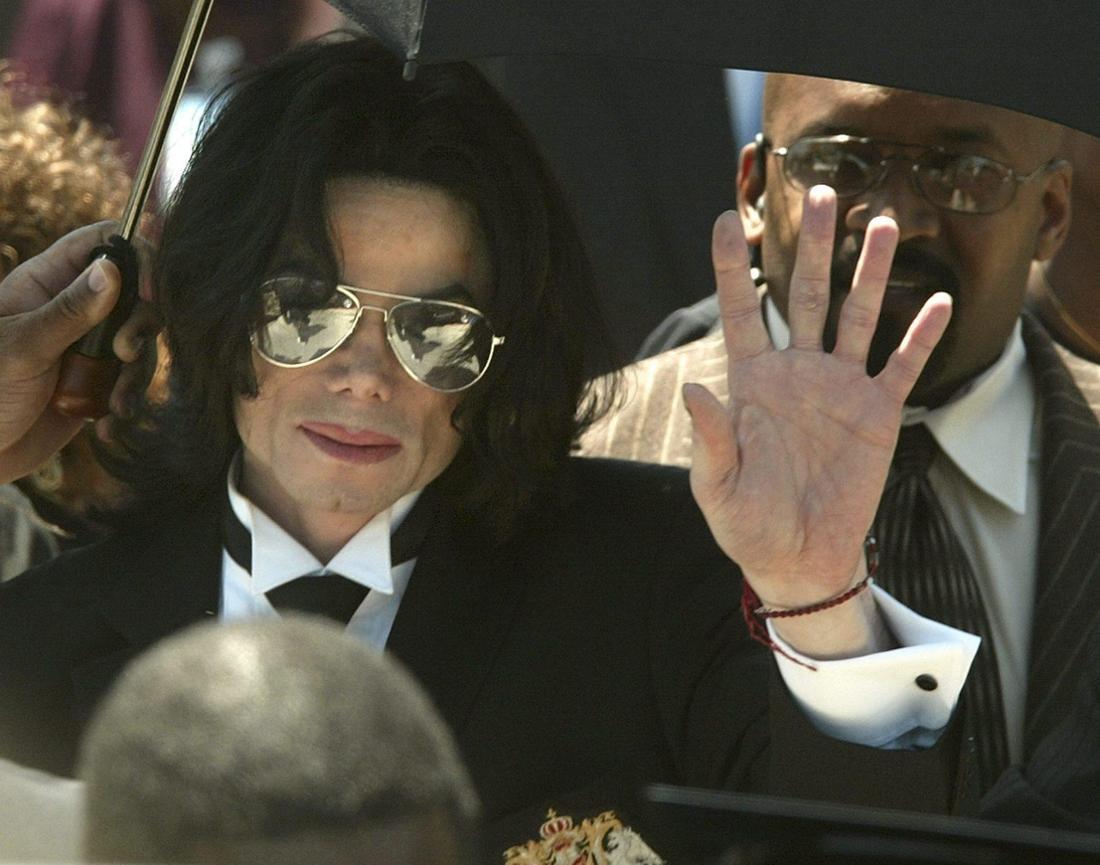 Michael Jackson ist von einer Menschenmenge umgeben und hebt die Hand zum Gruß