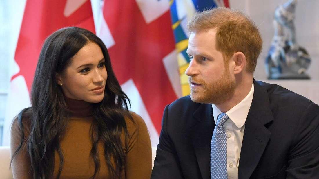 Meghan Markle und Prinz Harry sitzen nebeneinander