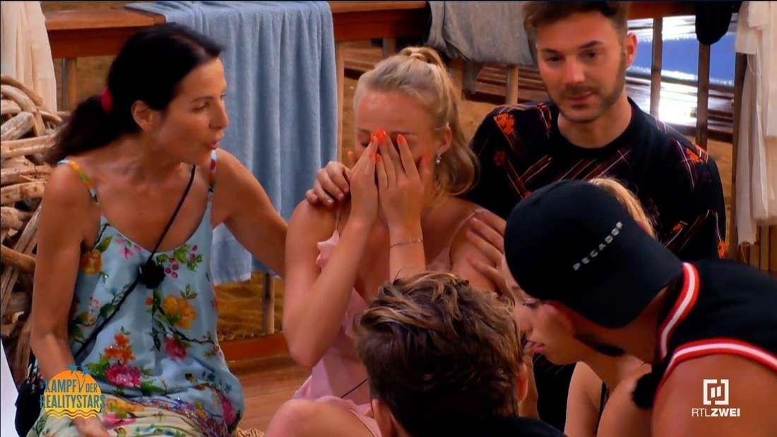 Yana schlägt die Hände vors Gesicht, sie wird getröstet von Sam und Andrea