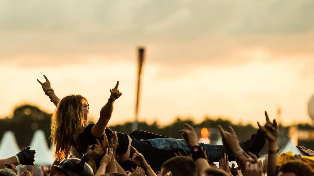 Ein Metalfan wird bei einem Konzert von der Menge getragen
