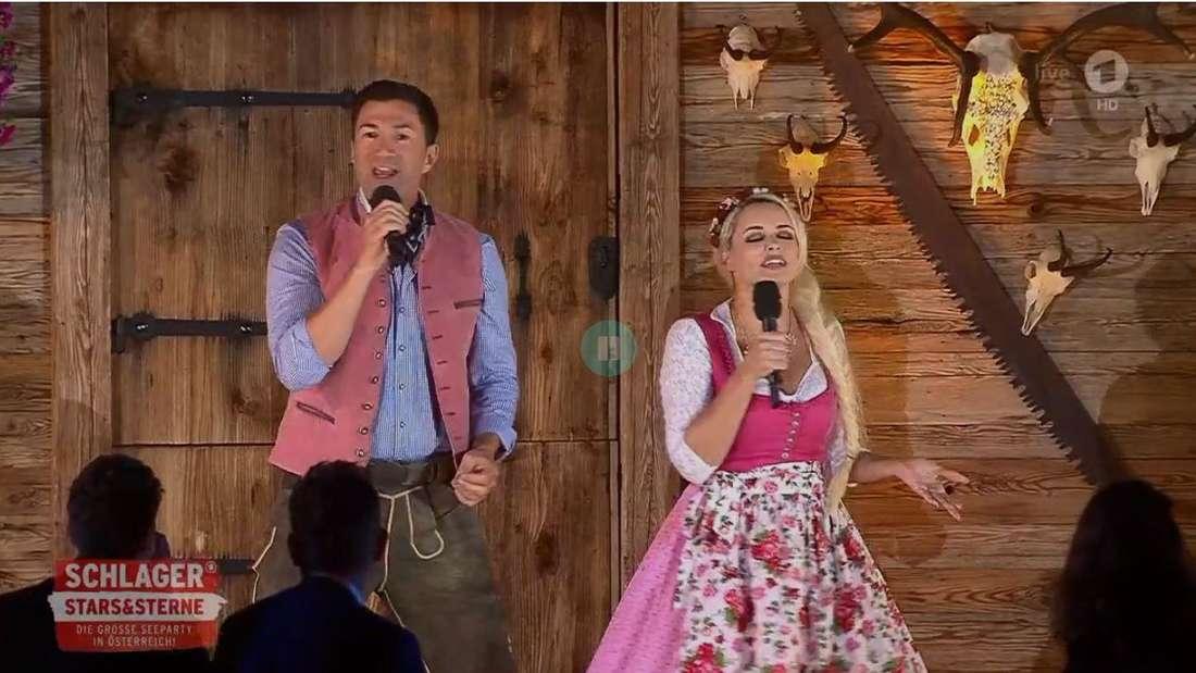 Daniela Katzenberger und Lucas Cordalis singen vor einer Holzhütte