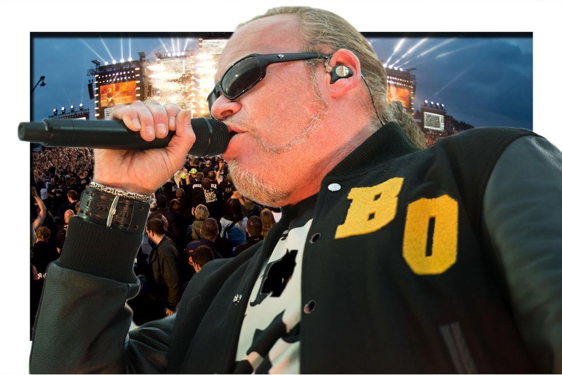 Im Vordergrund sieht man Böhse Onkelz-Frontmann Kevin Russell mit einem Mikrophon vor einem Bühnenaufbau mit Fans