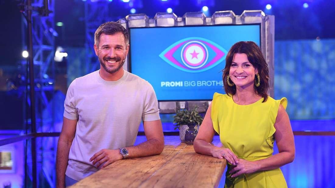 """Die Moderatoren Jochen Schropp und Marlene Lufen stehen im Studio vor dem Logo der Sendung «Promi Big Brother"""""""