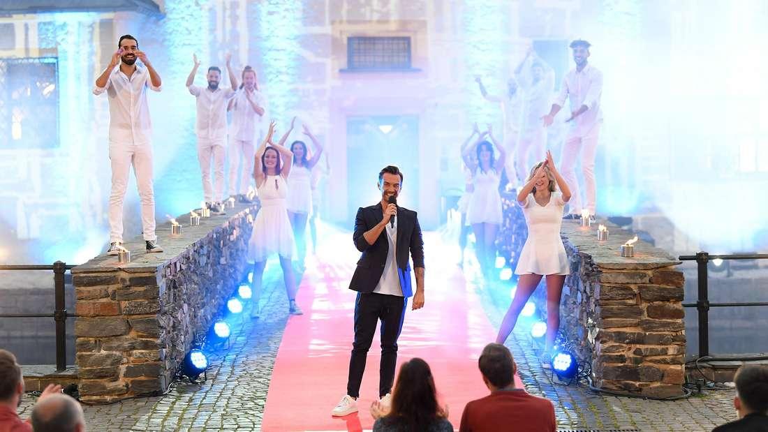 Florian Silbereisen bei einem Auftritt mit weiß gekleideten Tänzern vor einer Kulisse