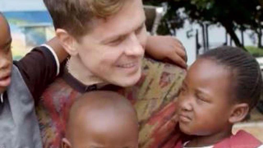 Michael Patrick Kelly ist umgeben von armen Kindern, für die er Spenden gesammelt hat