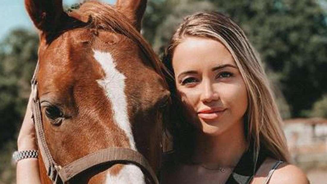 Cathy Lugner steht neben einem Pferd