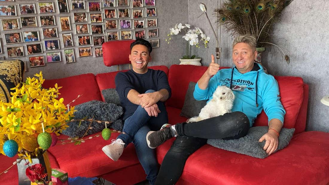 Hubert Fella sitzt mit seinem Mann Matthias Mangiapane auf einem roten Sofa. Hubert hat dabei einen weißen Hund auf seinem Schoß sitzen und streckt einen Daumen nach vorn.
