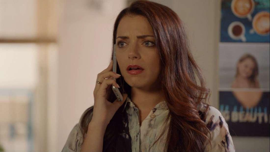 Emily am Handy, sie schaut entsetzt