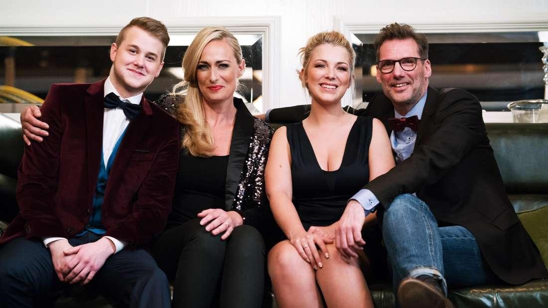 GZSZ: Jonas, Maren, Lili und Alex sitzen mit Anzug und Kleid auf einem Sofa und lächeln in die Kamera