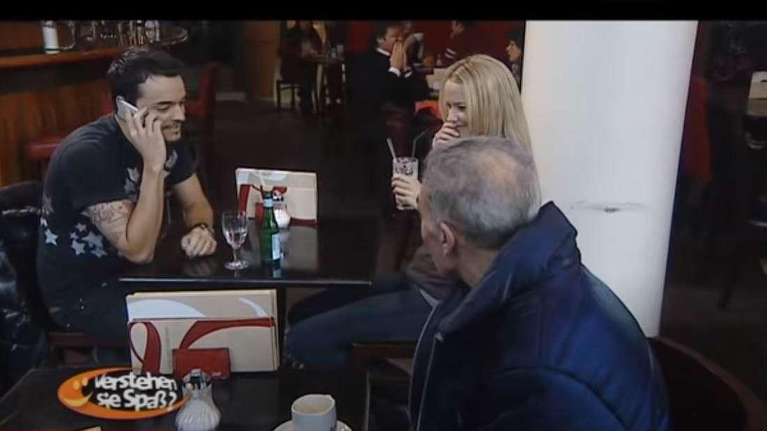Schlagersänger Giovanni Zarrella sitzt mit einer Blondine in einem Cafe und telefoniert mit seiner Frau Jana Ina Zarrella