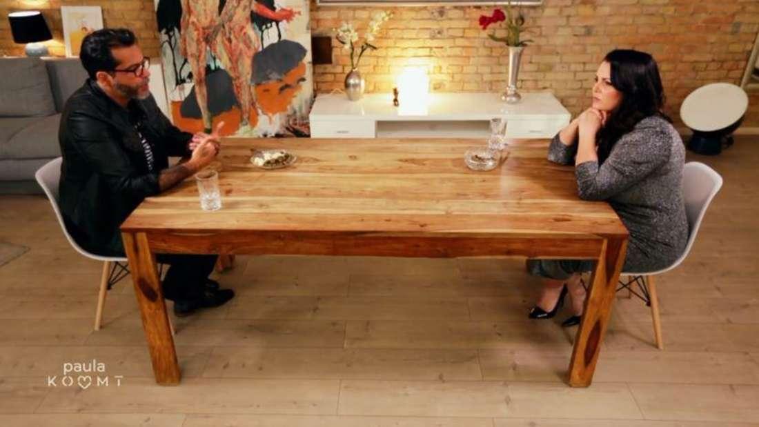 Aurelio Savina und Paula Lambert sitzen sich an einem Tisch gegenüber