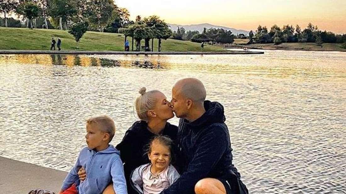 Oksana sitzt mit ihrem Mann und ihren beiden Kindern am Wasser