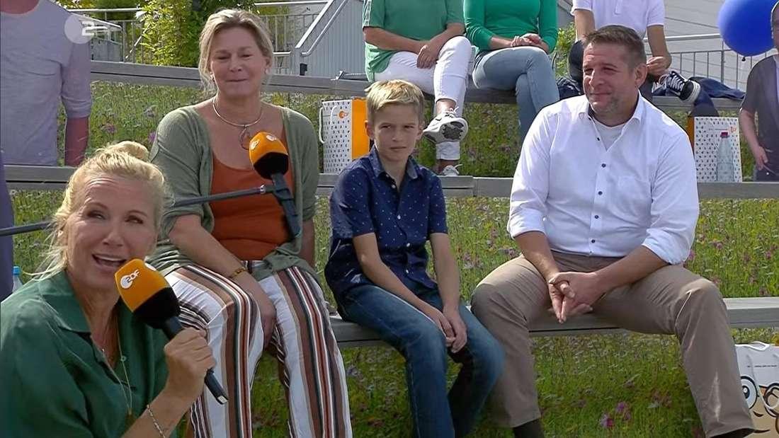 Andreas Kiewel sitzt gemeinsam mit einer Familie auf der Tribüne