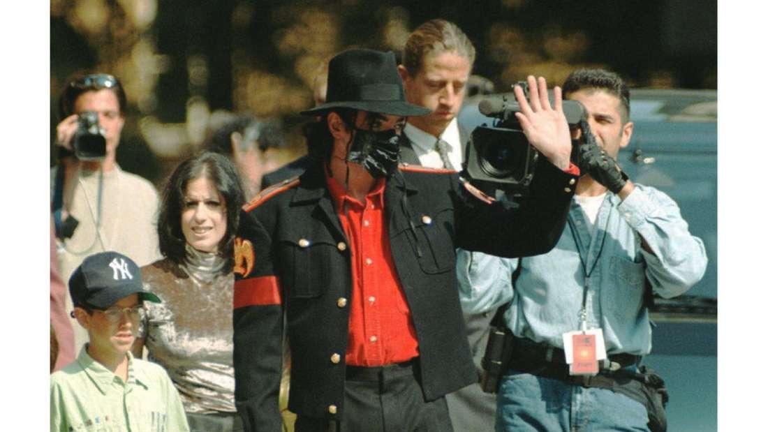 """Michael Jackson, der """"King of Pop"""" läuft in dunklem Anzug und Gesichtsmaske durch die Straßen Prags"""