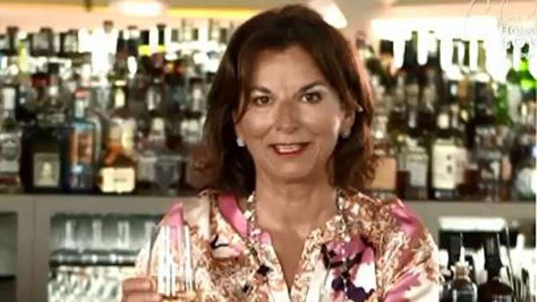 Claudia Obert sitzt an der Bar und hält ein Glas Sekt hoch