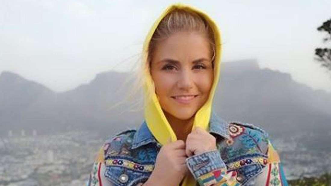 Beatrice Egli lächelt und steht auf einem Berg