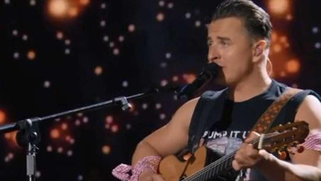 Andreas Gabalier singt auf der Bühne mit Gitarre