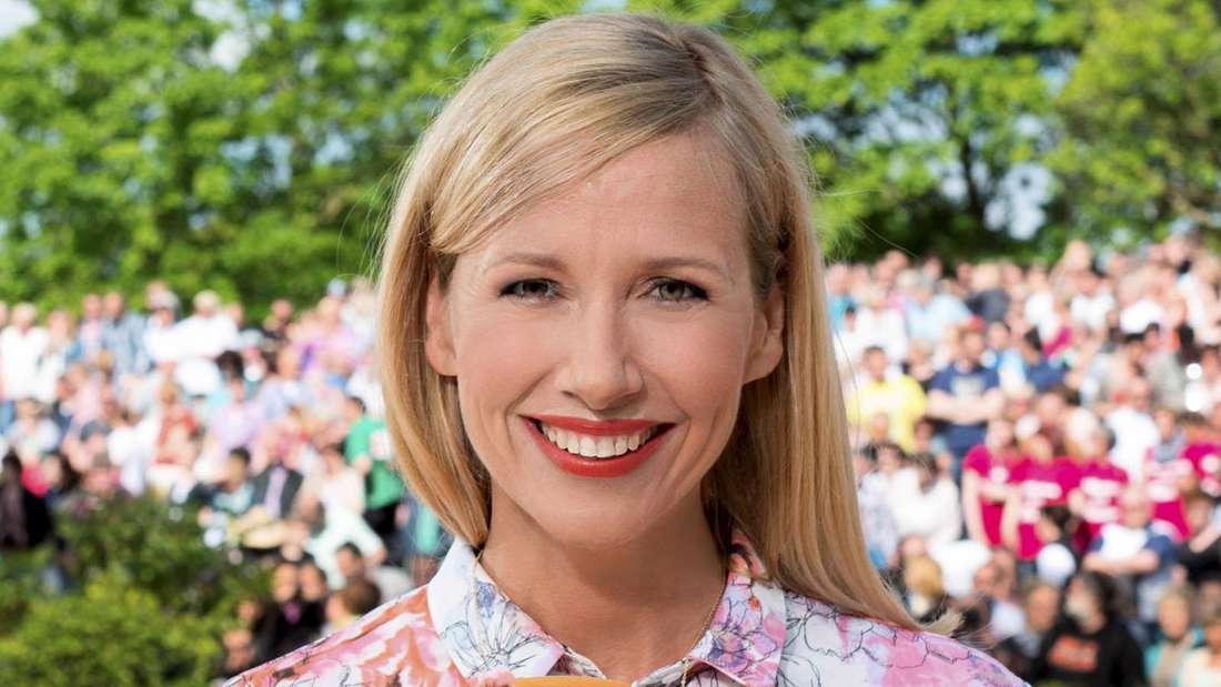 Andrea Kiewel mit dem ZDF-Mikro in bunter Kleidung und Schminke