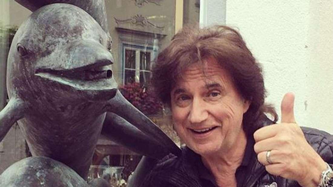 Olaf der Flipper posiert vor einer Delphin-Statue