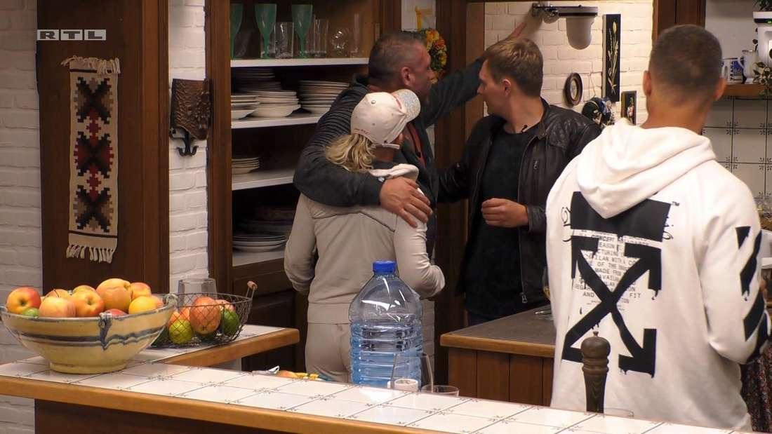 Caro und Andreas umarmen sich. Im Hintergrund sind andere Sommerhaus der Stars-Kandidaten zu sehen