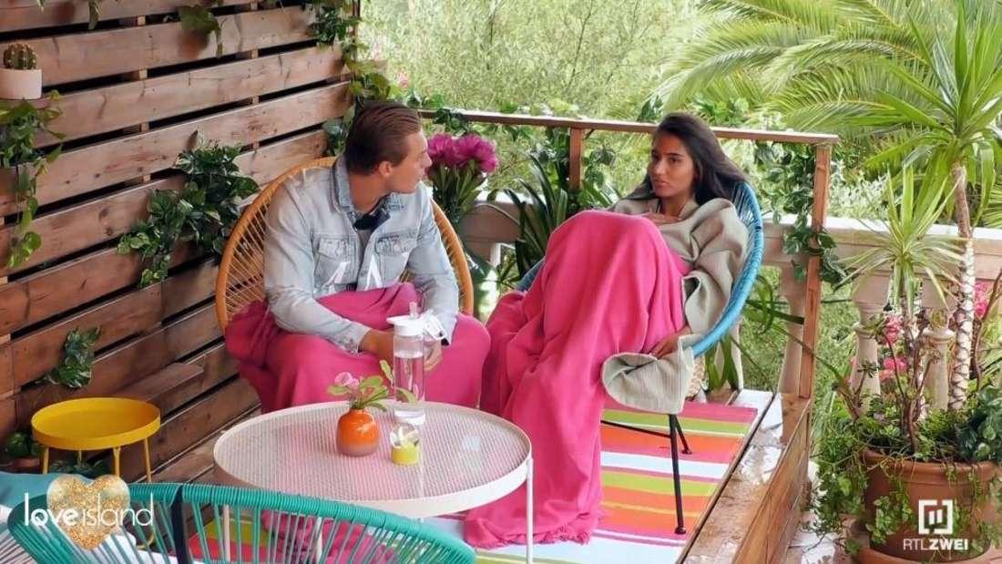 Aurelia und Henrik sitzen auf dem Balkon und unterhalten sich