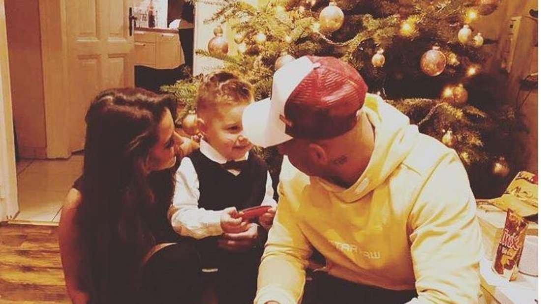Sarah, Pietro und Alessio Lombardi knien vor einem Weihnachtsbaum.