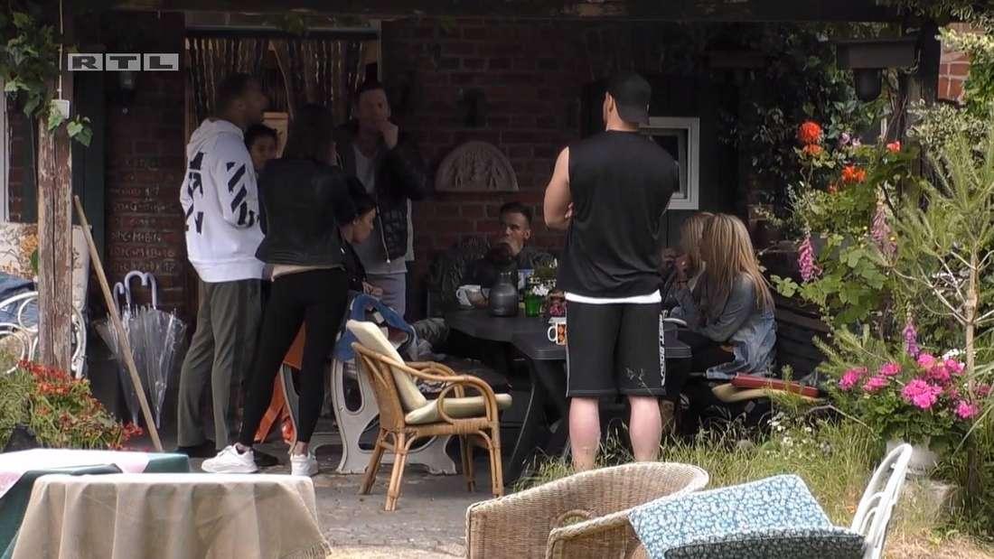 Die Teilnehmer stehen im Garten und diskutieren